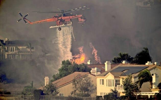 カリフォルニア州のロサンゼルス近郊で発生した山火事の鎮火にはヘリコプターも出動した=AP