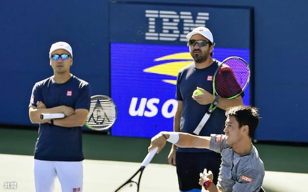 8月、マイケル・チャン・コーチ(左)、ダンテ・ボティーニ・コーチ(右奥)が見守る中、調整する錦織圭=ニューヨーク(共同)