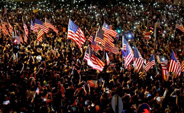 星条旗を掲げて米議会に「香港人権・民主主義法案」の可決を促す大集会(14日夜、香港セントラル)=ロイター