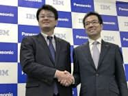 協業の発表会見で握手する日本IBMの山口明夫社長(左)とパナソニックの樋口泰行専務(15日、大阪市)