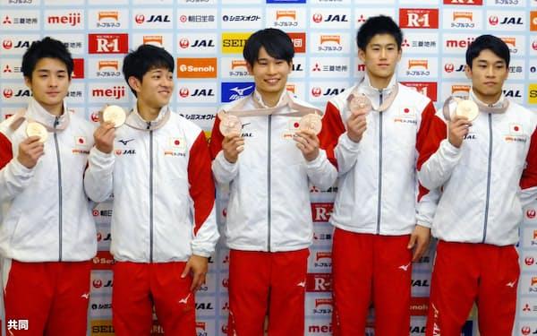 体操の世界選手権から帰国し、記者会見でメダルを手にする(左から)神本、谷川翔、萱、橋本、谷川航(15日、成田空港)=共同