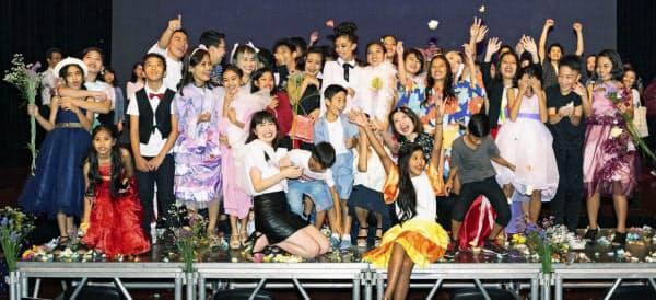 貧困層の子どもをモデルにしたファッションショーで記念写真に納まる西側さん(前列中央左)ら(2月、マニラ)=西側さん提供・共同
