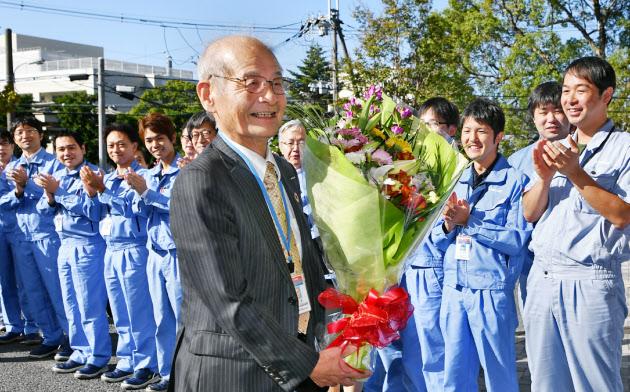 リチウムイオン電池材料評価研究センターで職員の出迎えを受け笑顔を見せる吉野彰さん(16日午前、大阪府池田市)