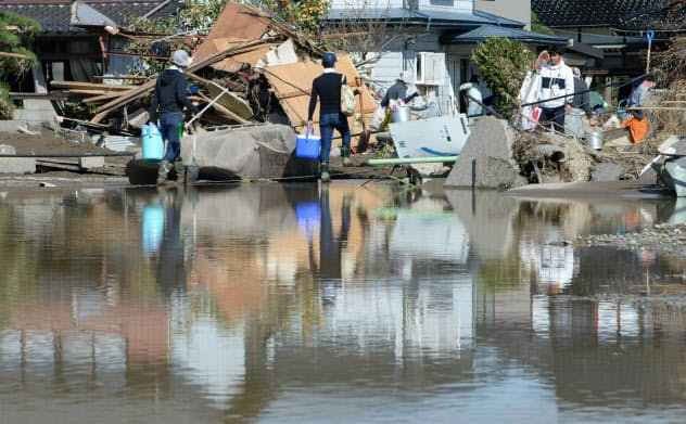 濁流が押し寄せ、水が残ったままの住宅地(16日午前、長野市)