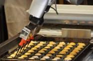 ロボットアームがたこ焼き生地や具材を鉄板に入れ、形を整えていく