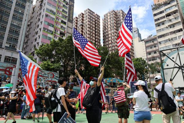 香港の民主派は米国の圧力に期待している(米国旗を掲げるデモ参加者)