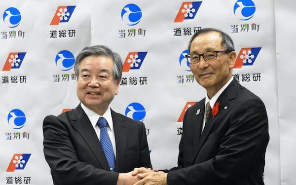 共同研究の調印式で握手する道総研の田中義克理事長(左)と当別町の宮司正毅町長(16日、札幌市)