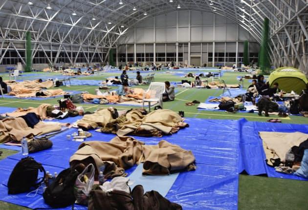 長野市の避難所で、寒さに耐えながら横になる人たち(13日夜)=共同