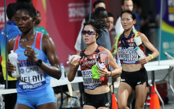 世界陸上の女子マラソンの給水ポイントでドリンクなどを受け取る日本人選手ら=山本博文撮影