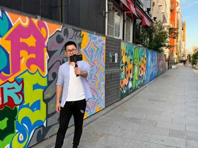壁に描かれた作品を前に写真を撮る通行人(大阪市)