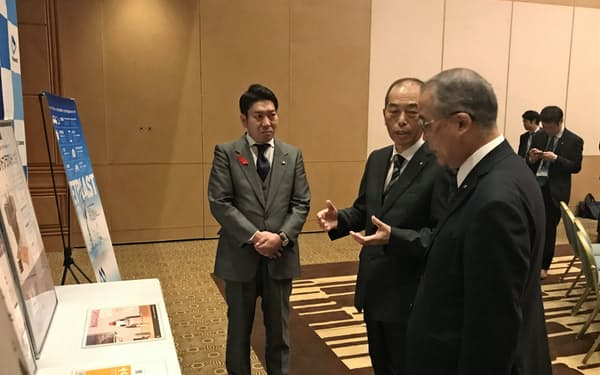 事業内容を長崎県の中村法道知事(右)らに説明する松原社長(10日、長崎市)