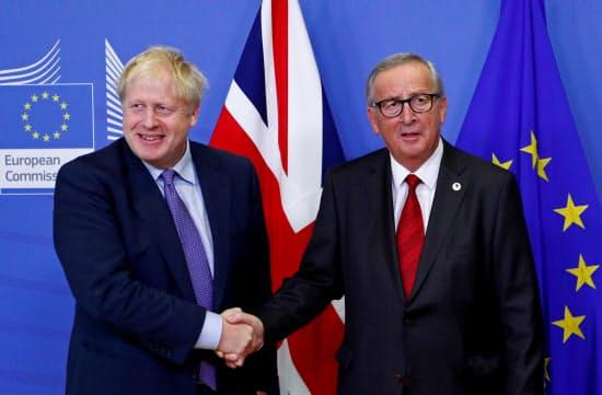 17日、離脱案合意後に握手するジョンソン英首相(左)とユンケル欧州委員長=ロイター