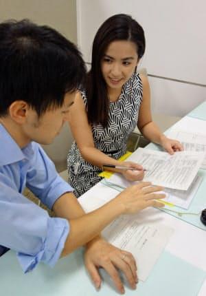 銀行口座を開こうとするチェー・ユントンさん(右)に、オトモの男性ガイドが通訳しながら手伝う(横浜市の銀行支店)