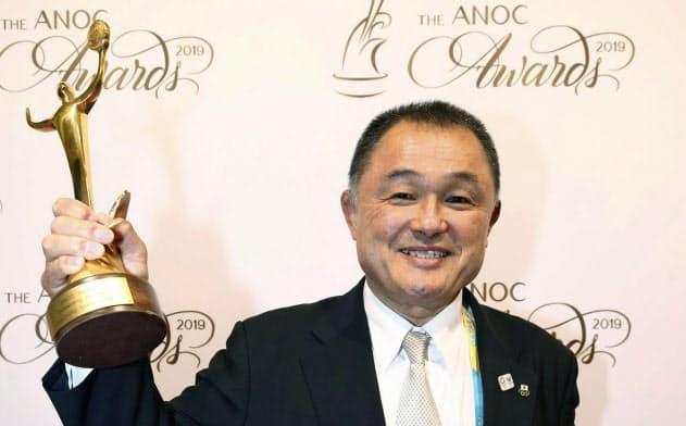 ANOCの年間表彰式で「卓越したアスリート賞」を受賞し、トロフィーを掲げるJOCの山下泰裕会長(17日、ドーハ)=ゲッティ共)