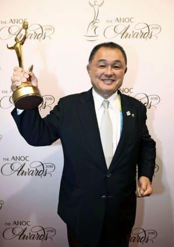 ANOCの年間表彰式で「卓越したアスリート賞」を受賞し、トロフィーを掲げるJOCの山下泰裕会長(17日、ドーハ)=ゲッティ共同