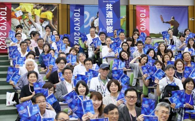 共通研修に参加し、ハンドブックを掲げる大会ボランティア(4日、東京・渋谷)