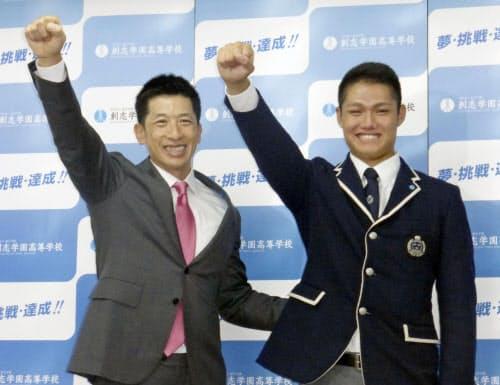 指名あいさつに訪れた阪神・矢野監督(左)とガッツポーズをする創志学園高の西純矢投手(18日、岡山市)=共同