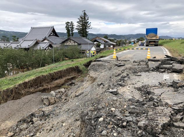 決壊した千曲川の堤防沿いに立つ妙笑寺(左)(15日、長野市)