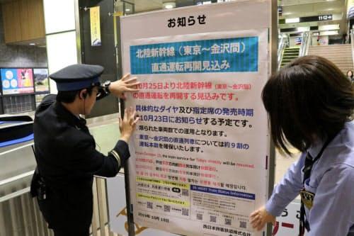 金沢―東京間の直通運転の再開見通しがたち、金沢駅でポスターを貼る駅員(18日午後、金沢市)