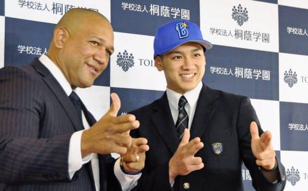 ドラフト1位指名のあいさつで訪れたDeNA・ラミレス監督(左)とポーズをとる桐蔭学園高の森敬斗内野手(18日、横浜市)=共同