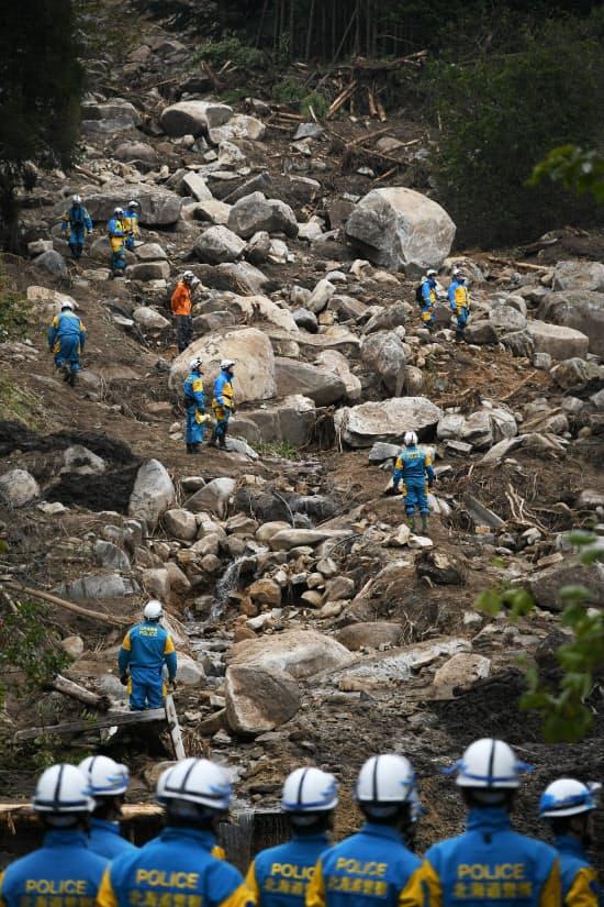 土砂崩れに巻き込まれた民家の周辺で行方不明者を捜索する警察官(18日、宮城県丸森町)