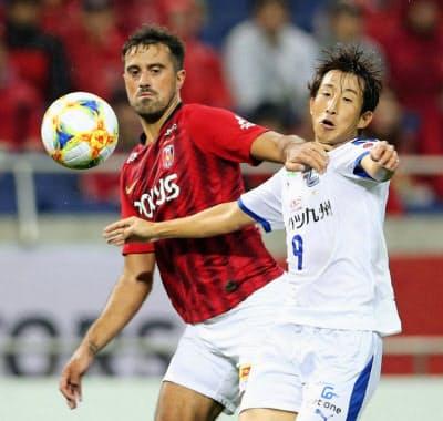 浦和―大分 前半、競り合う浦和・マウリシオ(左)と大分・後藤(18日、埼玉スタジアム)=共同