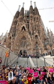 18日、サグラダ・ファミリア教会前でスローガンを叫ぶデモ参加者(バルセロナ)=ロイター