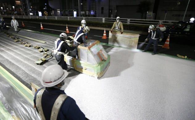 道路の表面に遮熱材を吹き付ける作業員(2015年7月、東京都内)=共同