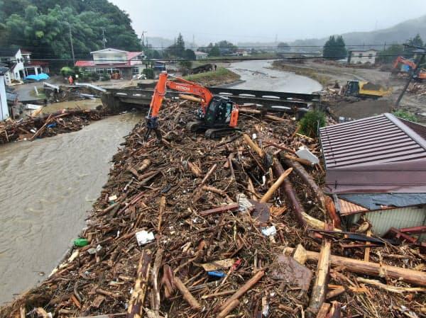 雨で増水した五福谷川で進む、流木の撤去作業(19日、宮城県丸森町)=浦田晃之介撮影