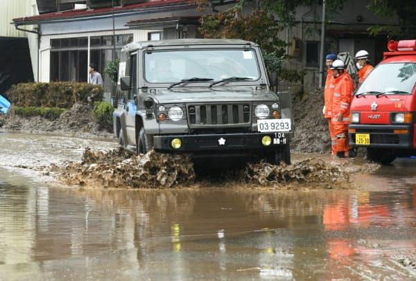雨で冠水した住宅地の道路(19日、宮城県丸森町)=浦田晃之介撮影