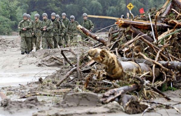 雨が降り続くなか、被害状況を確認する自衛隊員(19日、宮城県丸森町)=共同