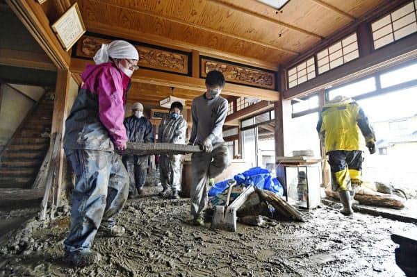 浸水被害にあった住宅で片付けをする人たち(19日、長野市)=共同