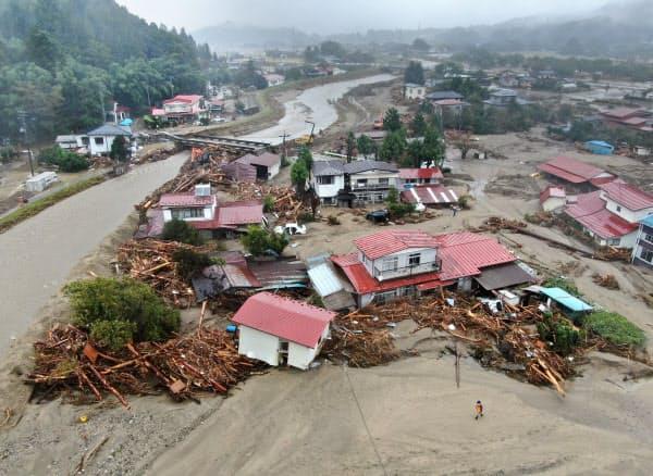五福谷川が氾濫し、大量の土砂と流木が押し寄せた住宅地(19日、宮城県丸森町)=浦田晃之介撮影