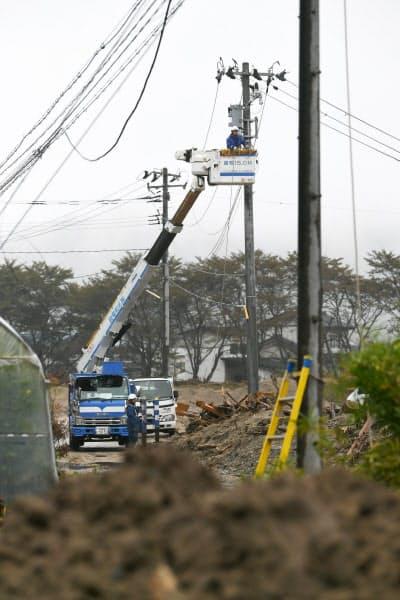 河川氾濫の被害を受けた住宅地で行われる電線の修復作業(19日、宮城県丸森町)=浦田晃之介撮影