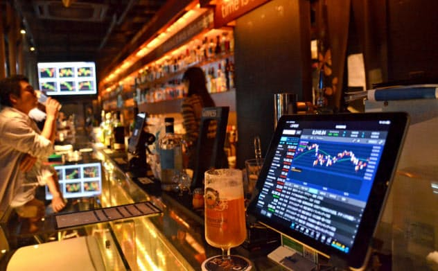 店内には株価や為替をリアルタイムで表示する端末や投資に関する書籍も(大阪市の「BarFPO」)