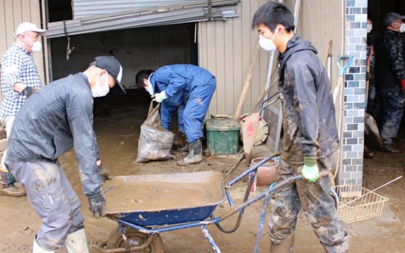 家屋に流入した泥をボランティアらが一輪車で何回も運び出す(19日、長野市)