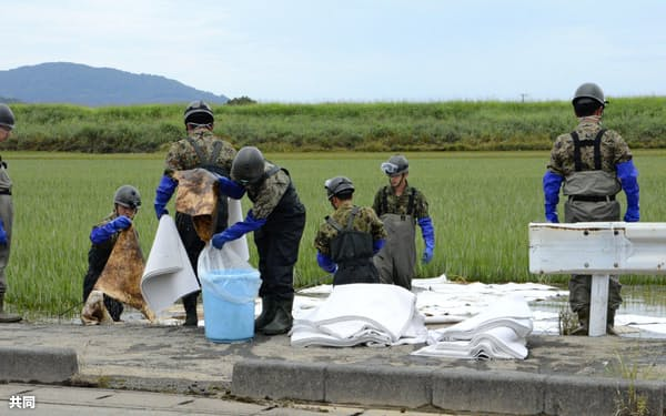 佐賀県大町町の水田で、鉄工所から流出した油の除去作業に当たる自衛隊員(8月31日)=共同
