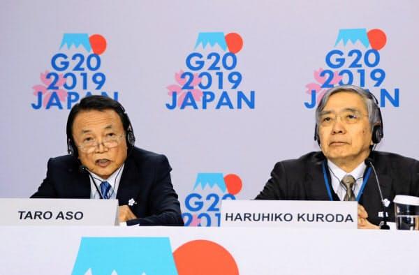 18日、米ワシントンで記者会見する麻生財務相(左)と日銀の黒田総裁=共同