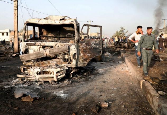 アフガニスタンではタリバンによる攻撃が相次いでいる(3日、首都カブールの爆弾テロ現場を歩く警察官ら)=ロイター