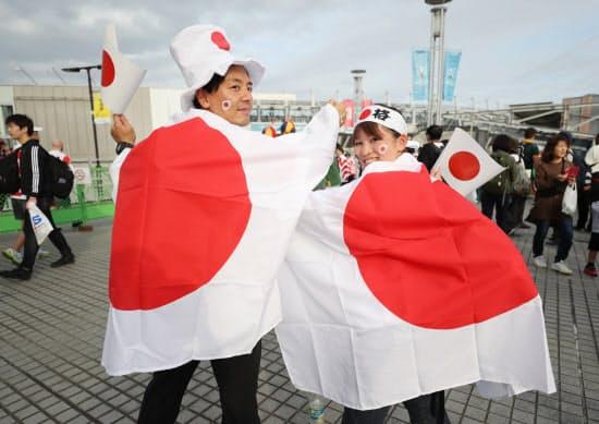 試合開始前、会場付近で日の丸を背負い盛り上がる日本のファン