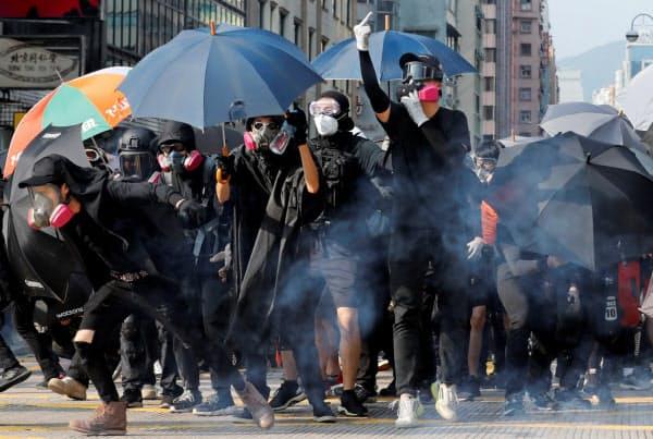 覆面禁止規則などに抗議する大規模デモが起きた(20日、香港)=ロイター