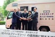 移動式薬局「モバイルファーマシー」の運用で八王子市などが連携する。(19日、東京都八王子市。中央は石森孝志・八王子市長、左は池野隆光・ウエルシアホールディングス会長)