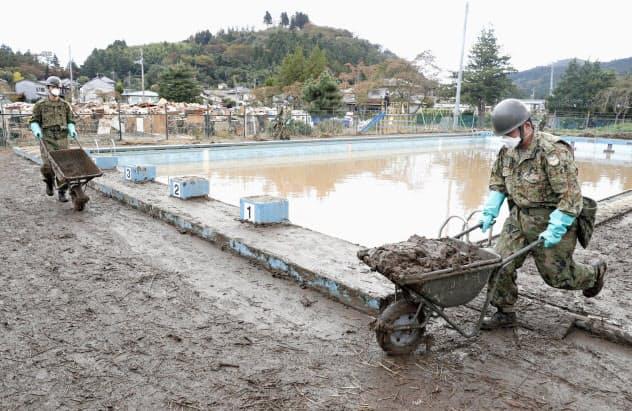 宮城県丸森町の金山小学校のプールで、清掃作業をする自衛隊員=20日午前