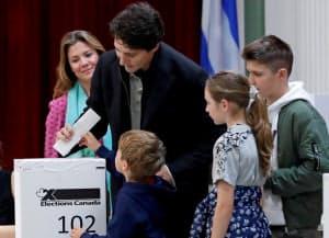 家族に見守られながら投票するトルドー首相(21日、モントリオール)=ロイター