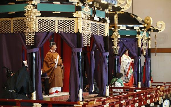 玉座「高御座」に立ち、「即位礼正殿の儀」に臨まれる天皇陛下。奥は「御帳台」に立たれる皇后さま(22日午後1時14分、宮殿・松の間)=代表撮影
