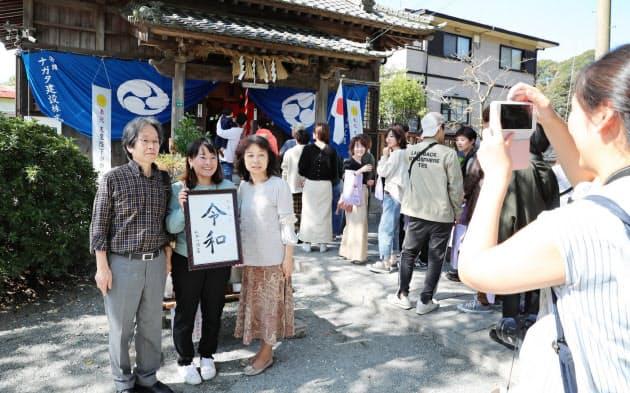 令和ゆかりの場所とされる坂本八幡宮で記念撮影する参拝客(22日、福岡県太宰府市)