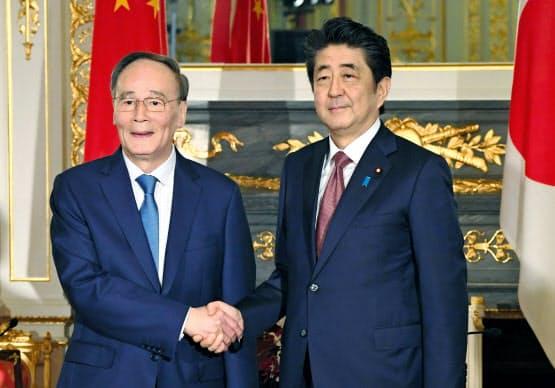 会談前に握手する安倍首相(右)と中国の王国家副主席(23日午前、東京・元赤坂の迎賓館)=代表撮影