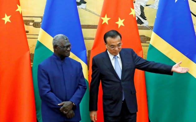 中国は太平洋島しょ国への外交攻勢を強める(ソロモン諸島のソガバレ首相=左=と中国の李首相)=ロイター
