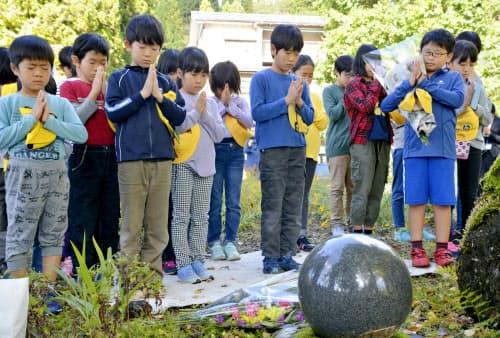 新潟県中越地震から15年となり、慰霊碑に手を合わせる市立東山小の児童たち(23日午後、新潟県小千谷市)=共同