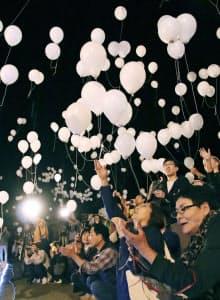 新潟県中越地震から15年、追悼式会場の近くでバルーンを飛ばす人たち(23日夜、新潟県長岡市)=共同